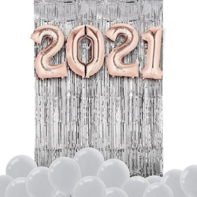 Create the ultimate party decoration with the Air-Filled Rose Gold 2020 Balloon Backdrop Kit! This kit includes everything you need to create a festive backdrop for a New Year's celebration or graduation party. Simply inflate balloons with air and attach them to a wall. Enjoy this helium free balloon decoration for 2-3 days. Do not use helium. Instructions not included with package. For instructions on how to assemble please see below. This kit includes:  2 Silver Fringe Doorway Curtain (SKU 4294) 15 Silver Pearl Balloons (SKU 632409) 1 26in Rose Gold 2020 Number Balloon Kit (SKU 857802)  Additional recommended supplies (sold separately):  Air pump (electric or hand-held) Double-sided tape or Scotch tape Scissors  To Assemble:  Attach fringe doorway curtain to a wall using tape. Inflate all balloons with air. (Balloon pump not included. Recommended for quick inflation.) Attach number balloons over fringe doorway curtain using tape. Scatter latex balloons on the floor around the backdrop.  Balloon Tip: Electric balloon pumps make inflation quicker; helium is not required.