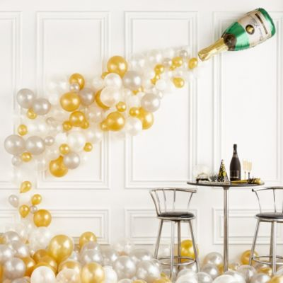 Create the ultimate party decoration with the Air-Filled Champagne Balloon Kit! This kit includes everything you need to create a festive backdrop for an anniversary party birthday party or New Year's celebration. Simply inflate balloons with air and attach them to the balloon arch decorating strip. Enjoy this helium free balloon decoration for 2-3 days. Do not use helium. Instructions not included with package. For instructions on how to assemble please see below. This kit includes:  1 Champagne Bottle Balloon (SKU 47086) 50 Mini White Balloons (SKU 186066) 20 Gold Pearl Balloons (SKU 632423) 20 Silver Pearl Balloons (SKU 632424) 50 Gold Pearl Mini Balloons (SKU 632461) 50 Silver Pearl Mini Balloons (SKU 632462) 20 White Balloons (SKU 71071) 1 Balloon Arch Decorating Strip (SKU 862880)  Additional recommended supplies (sold separately):  Air pump (electric or hand-held) Double-sided tape or Scotch tape Scissors  To Assemble:  Inflate all balloons with air and tie a knot at the end. (Balloon pump not included. Recommended for quick inflation.) Insert balloon lips into decorating strip holes and gently pull balloon knots through the holes to secure. Alternate balloon sizes and skip holes as needed on decorating strip as you attach balloons. Tie a long piece of curling ribbon to an empty hole at each end of the decorating strip and hang garland against a wall or from the ceiling. Apply tape to 5-inch balloons and fill in gaps on balloon garland. Attach the champagne bottle balloon above the latex balloons on the wall using tape.  Balloon Tip: Electric balloon pumps make inflation quicker; helium is not required.