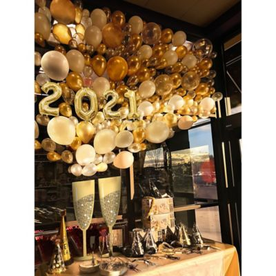 Create the ultimate New Year's Eve party decoration with the Air-Filled Champagne Prop Balloon Kit! This kit includes everything you need to create a festive backdrop for a New Year's celebration. Simply inflate balloons with air and attach them to a wall. Enjoy this helium free balloon decoration for 2-3 days. Do not use helium. Instructions not included with package. For instructions on how to assemble please see below. This kit includes:  1 Giant Glitter Gold Champagne Bottle Photo Booth Prop (SKU 804924) 2 13in Air-Filled Gold Number Balloon (2) (SKU 749353) 2 13in Air-Filled Gold Number Balloon (0) (SKU 749351) 50 Gold Pearl Mini Balloons (SKU 632461) 50 Silver Pearl Mini Balloons (SKU 632462) 15 Gold Pearl Balloons (SKU 632401) 15 White Pearl Balloons (SKU 632411)  Additional recommended supplies (sold separately):  Air pump (electric or hand-held) Double-sided tape or Scotch tape  To Assemble:  Tape champagne bottle prop to wall. Inflate all balloons with air and tie a knot at the end. (Balloon pump not included. Recommended for quick inflation.) Attach balloons to wall above bottle prop using tape.  Balloon Tip: Electric balloon pumps make inflation quicker; helium is not required.