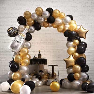 Create the ultimate New Year's Eve party decoration with the Air-Filled Black Gold & Silver New Year's Eve Balloon Arch Kit! This kit includes everything you need to create a festive backdrop or entryway for your New Year's celebration. Simply inflate balloons with air and attach them to the balloon arch. Enjoy this helium free balloon decoration for 2-3 days. Do not use helium. Instructions not included with package. For instructions on how to assemble please see below. For best results assemble on flat smooth surface. This kit includes:  1 Champagne Bottle New Year's Eve Balloon Bouquet (SKU 806228) 1 Balloon Arch Kit (SKU 744408) 30 Black Pearl Balloons (SKU 632396) 30 Gold Pearl Balloons (SKU 632401) 30 Silver Pearl Balloons (SKU 632409)  Additional recommended supplies (sold separately):  Air pump (electric or hand-held) Drill or screwdriver Water  To Assemble:  Build balloon arch frame using the instructions inside the Balloon Arch Kit. Air-inflate balloons and tie 4 together. Position your first layer at the bottom of one side of the arch.  Insert balloon lips into balloon disk holes.  Add layers using the same technique to complete arch.   Balloon Tip: Electric balloon pumps make inflation quicker; helium is not required.
