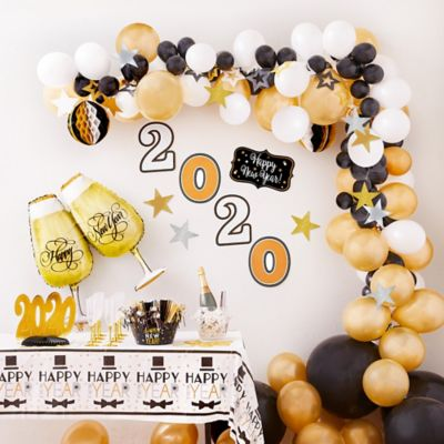 To view assembly instructions CLICK HERE. Give your party an instant wow-factor with the Air-Filled Black Gold & Silver New Year's Eve Balloon Garland Kit! This kit includes everything you need to make a beautiful balloon garland  no helium required. Use this kit to create backdrops centerpieces and entryway displays that last for 2-3 days. Do not use helium. Instructions not included with package. For instructions on how to assemble please see below or refer to the 'Instructions' image on this page. This kit includes:  30 Gold Pearl Balloons (SKU 632401) 4 Black Balloons (SKU 632428) 50 Black Mini Balloons (SKU 632447) 20 White Balloons (SKU 71071) 1 Metallic Silver Curling Ribbon Keg (SKU 789023) 1 Black Gold & Silver 2020 New Year's Room Decorating Kit (SKU 185533) 1 Foil New Year's Toast Balloon (SKU 185566) 18 Glitter New Year's Cutouts (SKU 455462) 1 Dapper Night Happy New Year Table Cover (SKU 804920) 1 Balloon Arch Decorating Strip (SKU 862880)  Additional recommended supplies (sold separately):  Air pump (electric or hand-held) Double-sided tape or Scotch tape Scissors  To Assemble:  Inflate all balloons with air and tie a knot at the end. (Balloon pump not included. Recommended for quick inflation.) Insert balloon lips into decorating strip holes and gently pull balloon knots through the holes to secure. Alternate balloon sizes (9-inch 12-inch and 24-inch) and skip holes as needed on decorating strip as you attach balloons. Tie a long piece of curling ribbon to an empty hole at each end of the decorating strip and hang garland against a wall or from the ceiling. Apply tape to 5-inch balloons and fill in gaps on balloon garland.  Decorating Tip: Enhance balloon garlands by adding balloon tassels flowers foliage swirl decorations and tassel garlands to balloons using tape! Accessories sold separately.