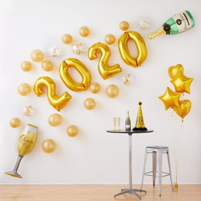 Create the ultimate New Year's Eve party decoration with the Air-Filled Gold Champagne New Year's Eve Balloon Kit! This kit includes everything you need to create a festive backdrop for a New Year's celebration. Simply inflate balloons with air and attach them to a wall. Enjoy this helium free balloon decoration for 2-3 days. Do not use helium. Instructions not included with package. For instructions on how to assemble please see below. This kit includes:  15 Gold Pearl Balloons (SKU 632401) 5 Ginger Ray Gold Confetti Balloons (SKU 830599) 2 Gold Curling Ribbon (SKU 474074)  Additional recommended supplies (sold separately):  Air pump (electric or hand-held) Double-sided tape or Scotch tape  To Assemble:  Inflate all balloons with air and tie a knot at the end. (Balloon pump not included. Recommended for quick inflation.) Attach balloons to wall using tape or hang using curling ribbon.  Balloon Tip: Electric balloon pumps make inflation quicker; helium is not required.